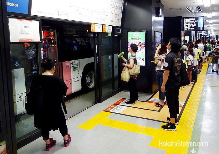 Passengers check bus departure times on the first floor of the Hakata Bus Terminal