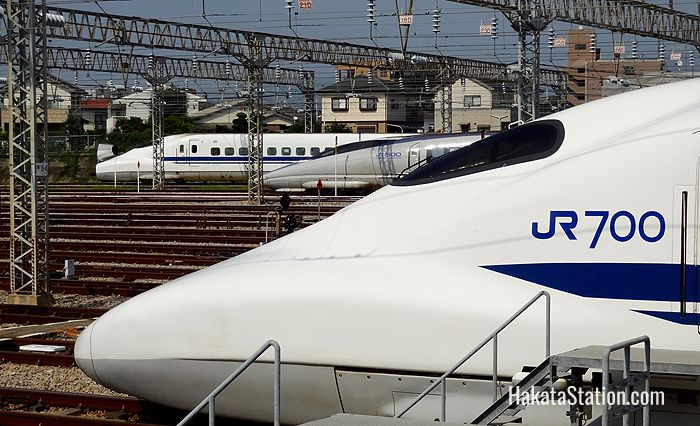 500 and 700 series Shinkansen trains at Hakata-Minami Station. The one at top right has its nose cone open.