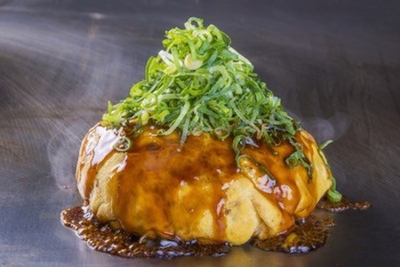 Denko-Sekka's signature dish is packed with meat, eggs, squid, cheese and topped with spring onions