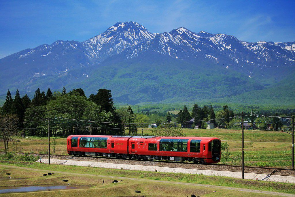 A beautiful train in a beautiful setting. The body of the train is colored vermilion to offer a warm contrast with the surrounding natural scenery
