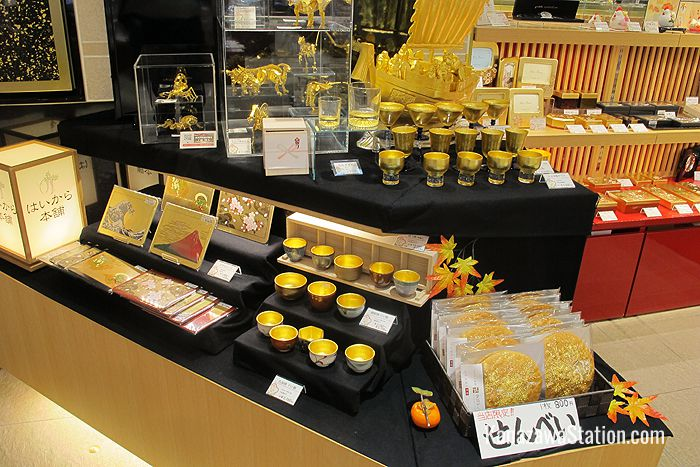 Gold leaf goods on display include ornaments, lacquerware with gold leaf inlay, and even (on the lower right) big round rice crackers decorated with flecks of gold!