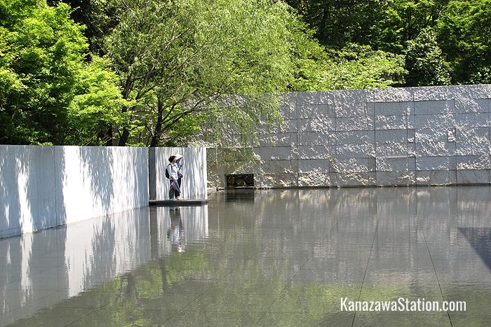 Natural greenery surrounds the white concrete walls and the reflective pool