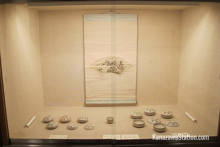 White porcelain bowls are displayed below a fan painting by the daughter of Kurando Terashima