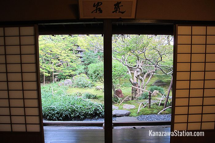 A garden view. The sign above the entrance to the garden reads kensen