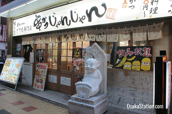 A typical local restaurant, Kushikatsu Janjan, with a Billiken statue outside