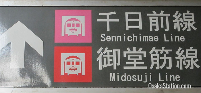 Signs for the Sennichimae Line are color-coded pink and signs for the Midosuji Line are red
