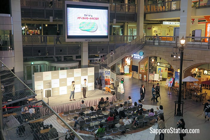 Two comedians entertain shoppers from the Atrium's event stage