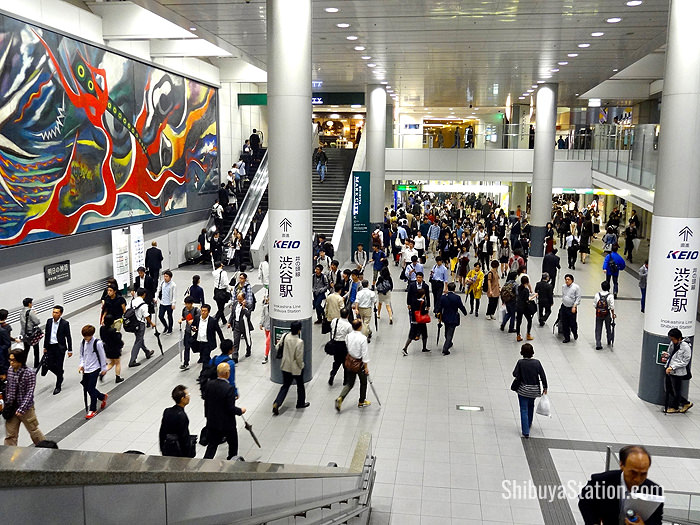 A mural-adorned elevated passageway connects JR and Keio stations at Shibuya