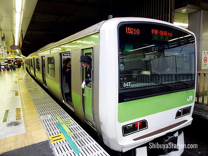 A Shinjuku-bound Yamanote Line train stops at Shibuya Station