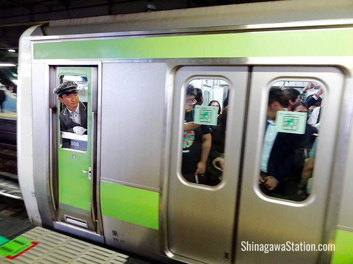A Yamanote loop line train stops at JR Shinagawa Station