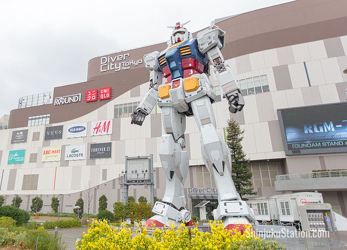 A statue of Gundam, the iconic robot from the anime franchise Mobile Suit Gundam towers over visitors in Odaiba