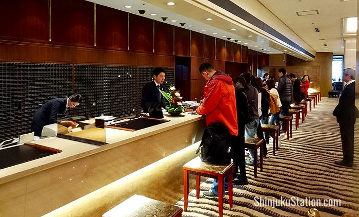 The lobby's front desk bustles with uniformed staff